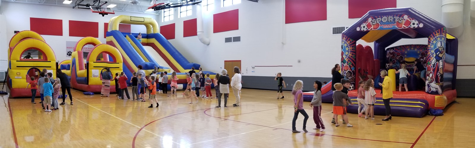 Students playing on inflatables during the Cougar Club carnival