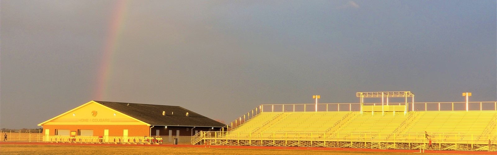 VWCS track stadium and concession stand with a rainbow in the background