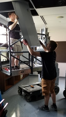 Workers install new lighting in a middle school classroom
